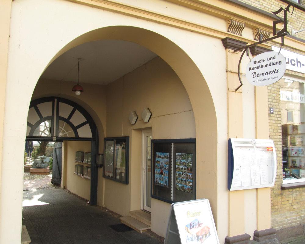 Neben der Buchhandlung geht es unter einem Torbogen hindurch in den Hinterhof zum Kneipenrestaurant.