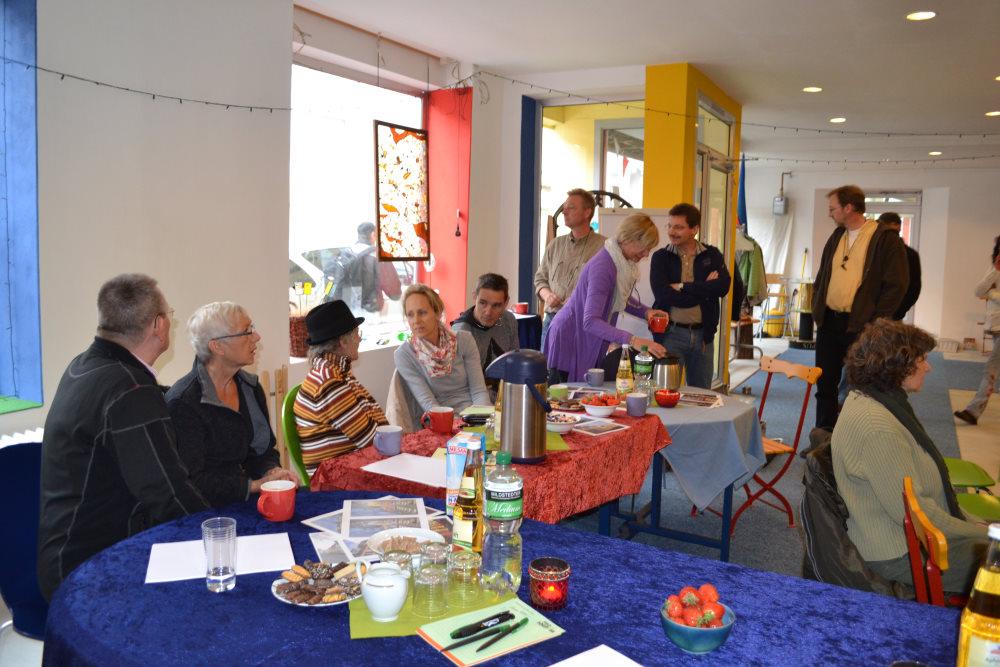 In den farbigen Räumlichkeiten vom KuKoLo sitzen und stehen Personen und unterhalten sich an Tischen mit Naschkram und Papieren.