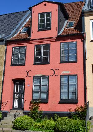 Das Gebäude im Lollfuß Nr. 92 mit kleiner Steintreppe und markantem altrosa Anstrich.