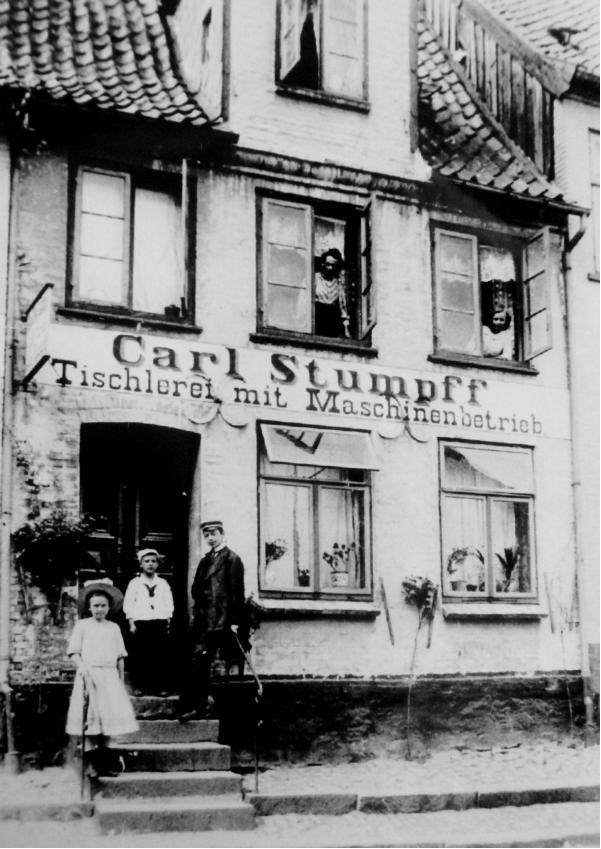 Ein altes Schwarzweiß-Foto des Hauses Lollfuß Nr. 92 um 1910, auf dem einige Personen aus den Fenstern schauen und vor dem Haus auf der treppe stehen.