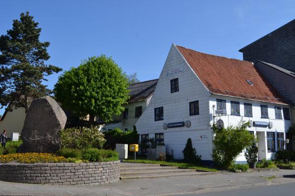 Aktuelle Ansicht des Gebäudes an der Kreuzung Flensburger Straße / Lollfuß mit dem Gedenkstein davor.