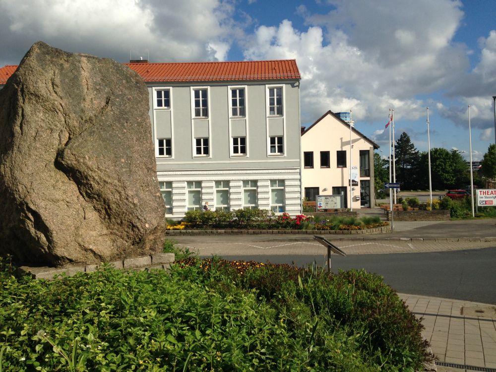Im Vordergrund ist die Seite des Steins zu sehen, im Hintergrund das Slesvihus auf der anderen Straßenseite.