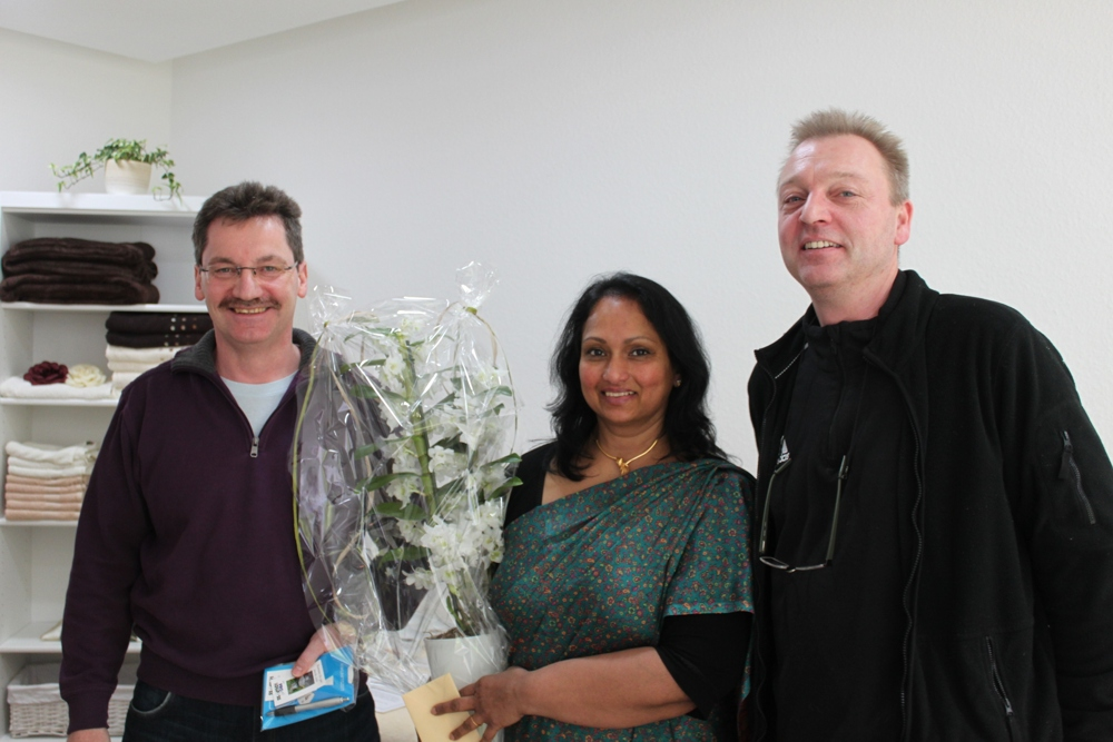 Ein Foto der Blumenübergabe, auf dem Frau Wickramatilleke zwischen den beiden Herren vom Pro-Lollfuß-Vorstand steht.