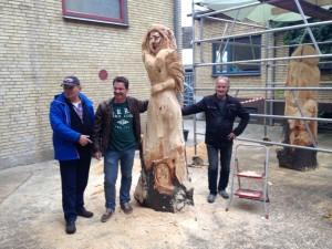 Neben dem aufrechtstehenden Lindenstamm, der schon deutlich eine Frauenfigur zeigt, stehen drei Männer in einem Hof.