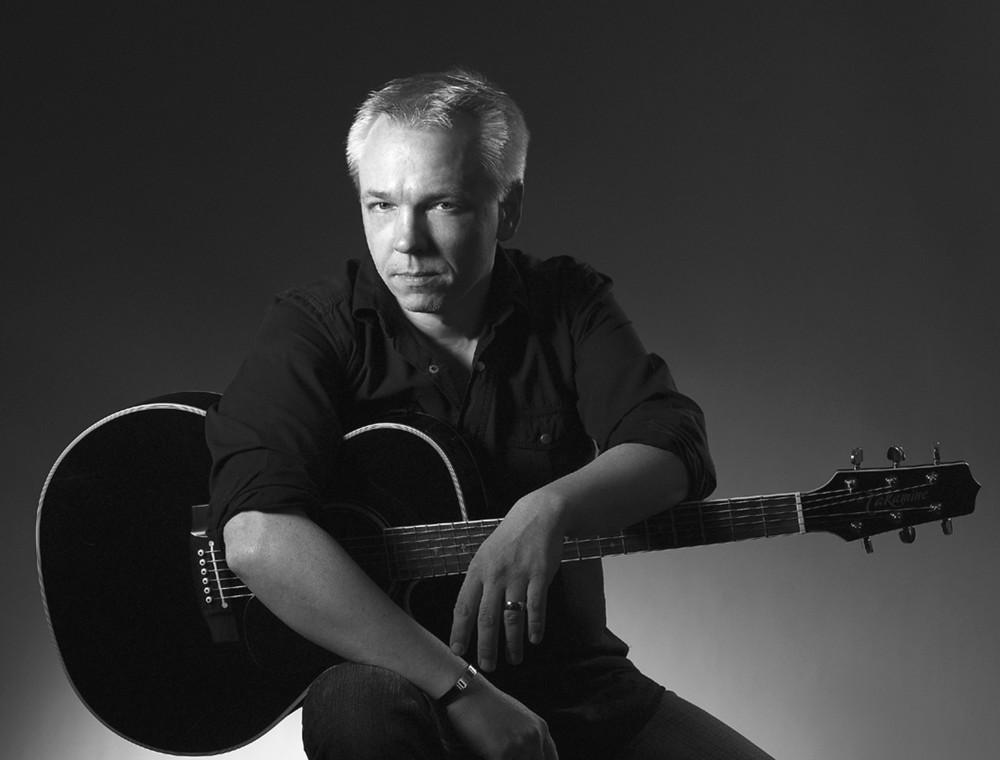 Ein stimmungsvolles Schwarz-Weiß-Foto zeigt den Musiker, der sich sitzend über seine dunkle Gitarre lehnt.