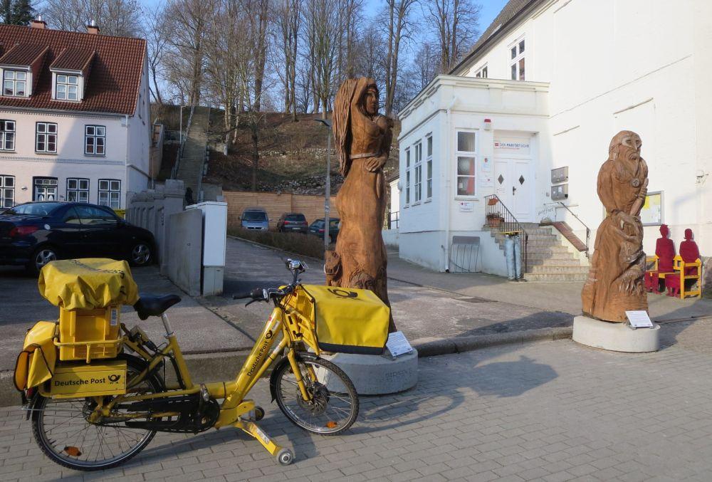 Vor den beiden übermannshohen Holzskulpturen am Fuß der Lollfußtreppe parkt ein Postbotenfahrrad.