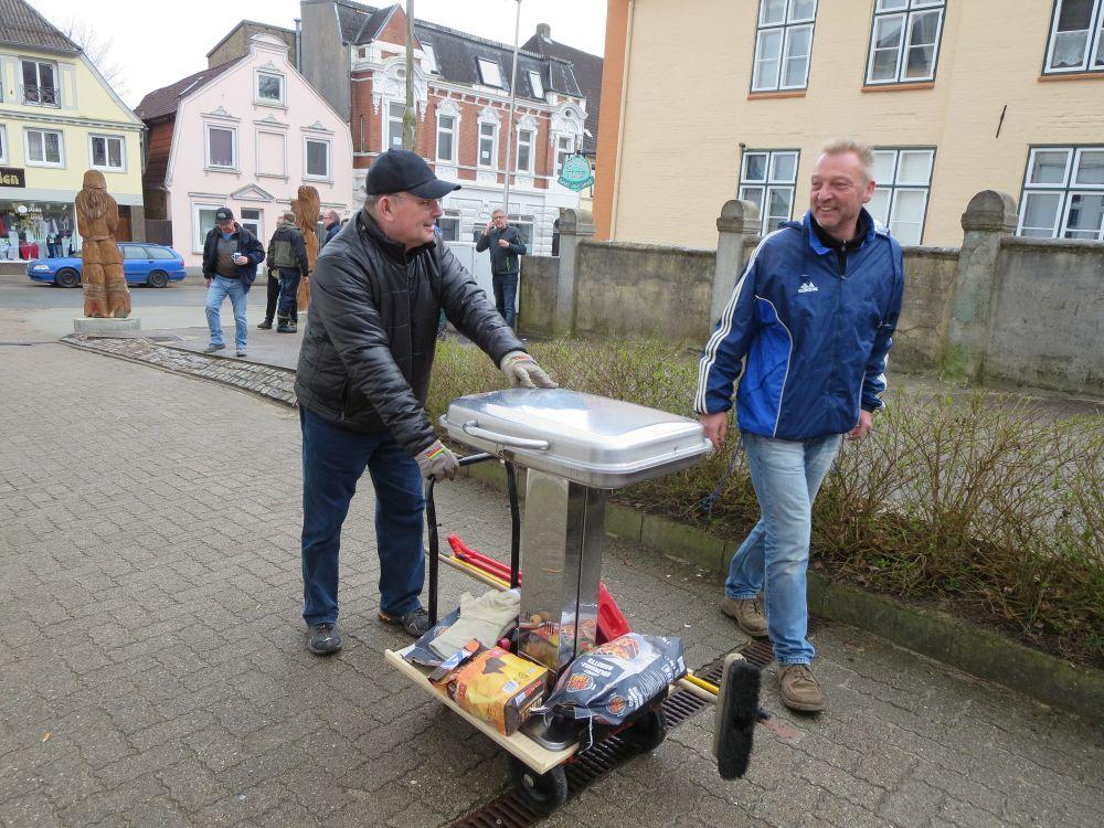 Zwei Männer schieben lachend einen Standgrill, der mit Zubehör auf einem Waren steht.