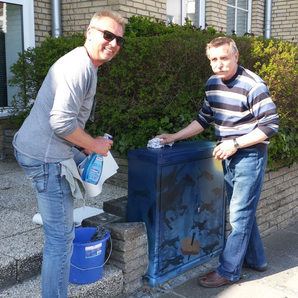 Zu sehen ist, wie die beiden Männer vor dem Bekleben die Oberfläche des Kastendeckels reinigen.