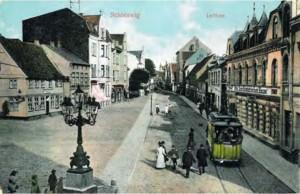Eine Postkarte aus der Ausstellung, die ein Foto mit Blick von der Kreuzung Lollfuß / Flensburger Straße in den Lollfuß hinein zeigt.