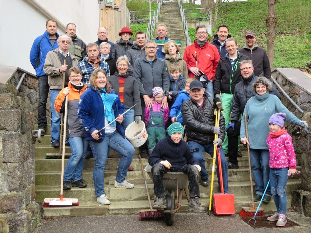 Eine Gruppe lachender Menschen, Erwachsene und Kinder, posieren mit ihren Arbeitsgeräten auf einer Treppe.