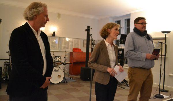 Eine Frau und zwei Männer stehen am Mikro auf der Bühne