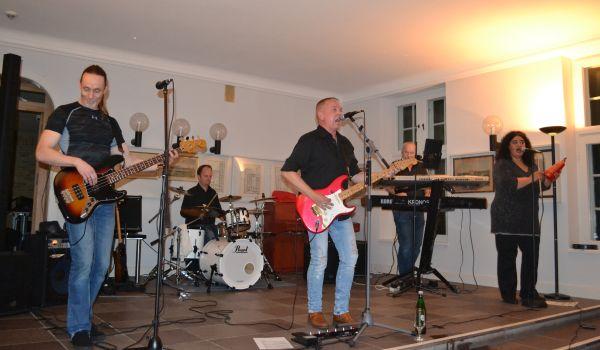 Fünf Menschen auf der Bühne, die durch den Hintergrund erkennen lässt, dass es sich eigentlich um den Kaminsaal des Amtsgerichtes handelt. Sie spielen zwei Gitarren, Schlagzeug, Keyboards undPercussion, mehrere von ihnen haben ein Gesangsmikro vor sich.