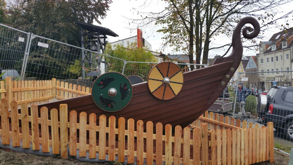 Seitenansicht des Bootes, jetzt mit Holz beplankt. Es hat bubt bemalte Schilde an den Seiten ind eine spiralförmige Bugverzierung. Ein Holzzaun hat jetzt den Bauzaun aus Metall ersetzt.