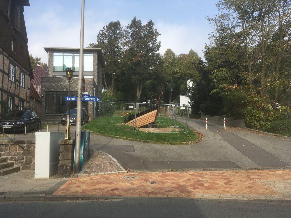 Ansicht der Wegkreuzung Lollfuß / Stadtweg / Fußweg zur Michaelisallee / Domziegelhof, wo aus der Rasenfläche heraus der Schiffsbug aus dem Hang herauszukommen scheint.