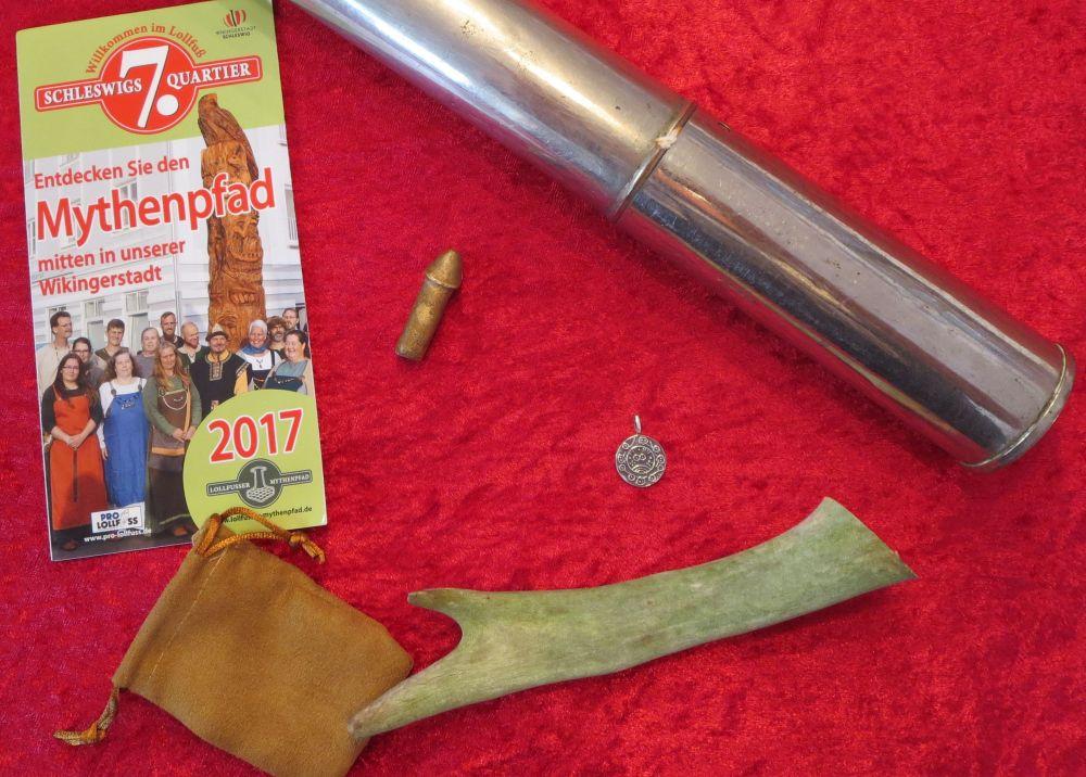 Neben einer gedruckten Broschüre üner den Mythenpfad zeigt das Bild den Inhalt einer Metallkapsel: ein Stück Geweih, eine silberne Münze und einen kleinen Phallus aus Bronze.